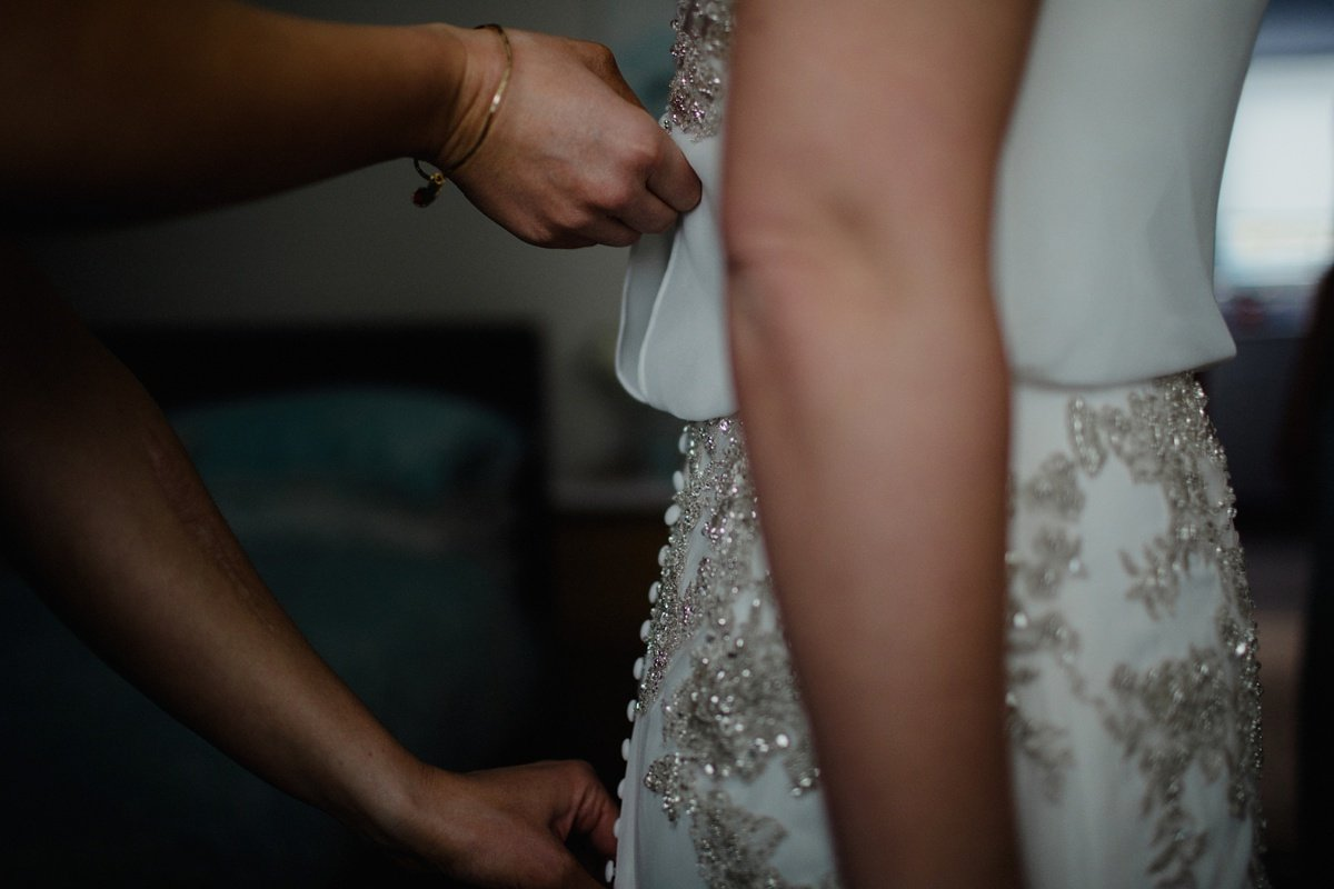 beaded wedding dress getting zipped up by bridesmaid