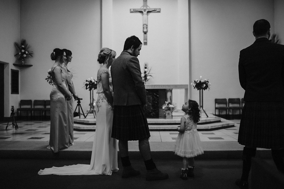 groom's daughter looks up at him at their church wedding, bride and groom at the altar