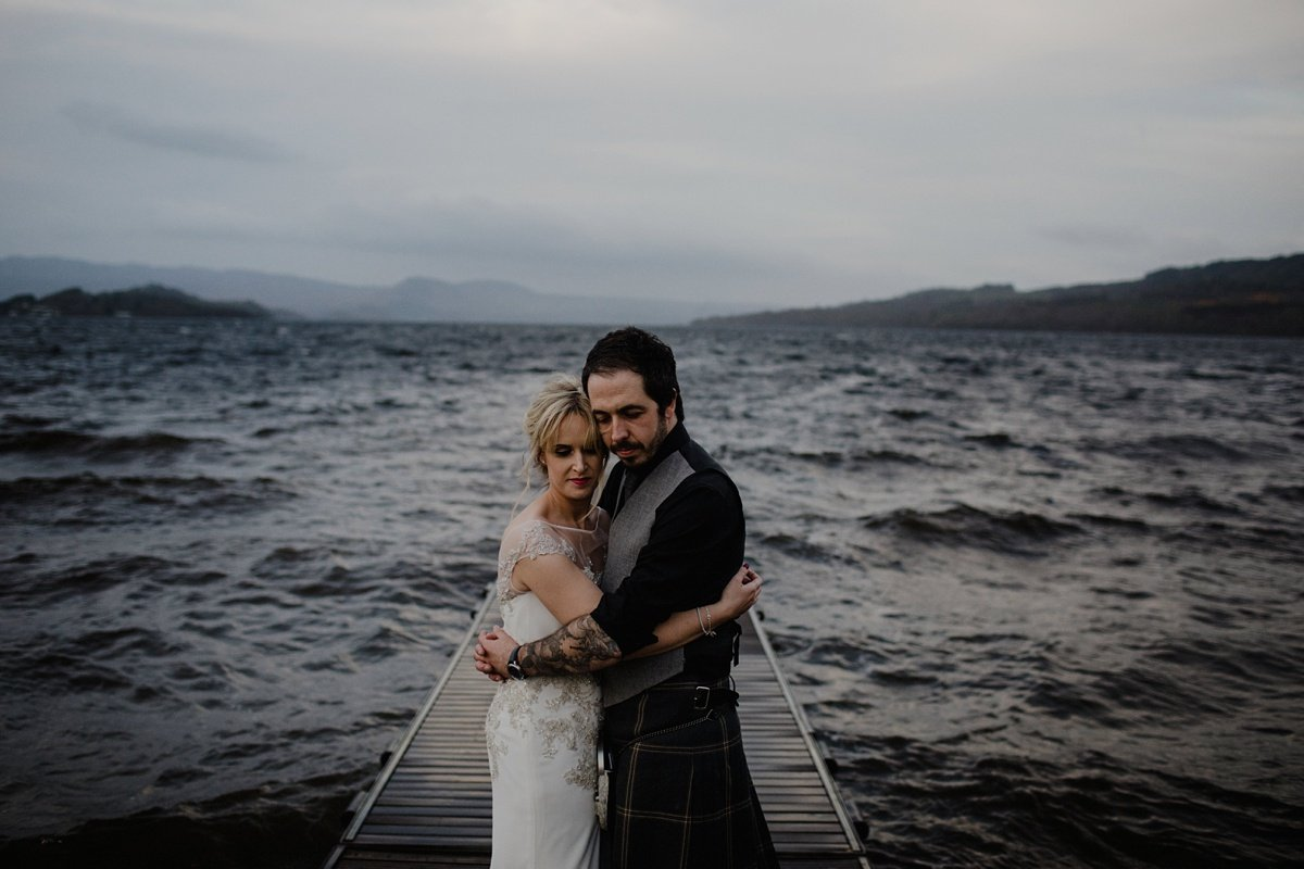bride and groom on the jetty in stormy waters for their wedding at the cruin loch lomond