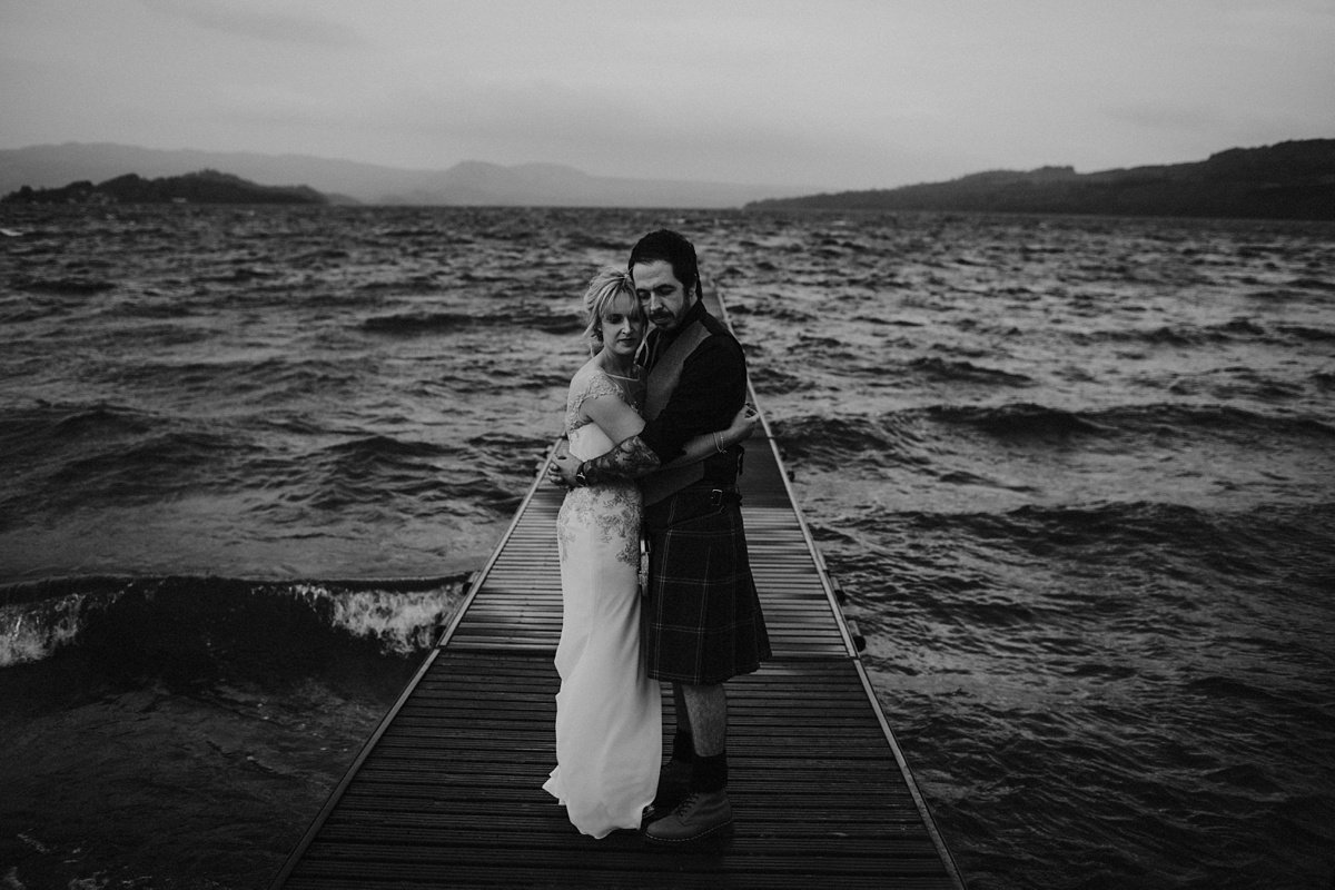 black and white image of bride and groom hugging on the jetty at their wedding at the cruin loch lomond