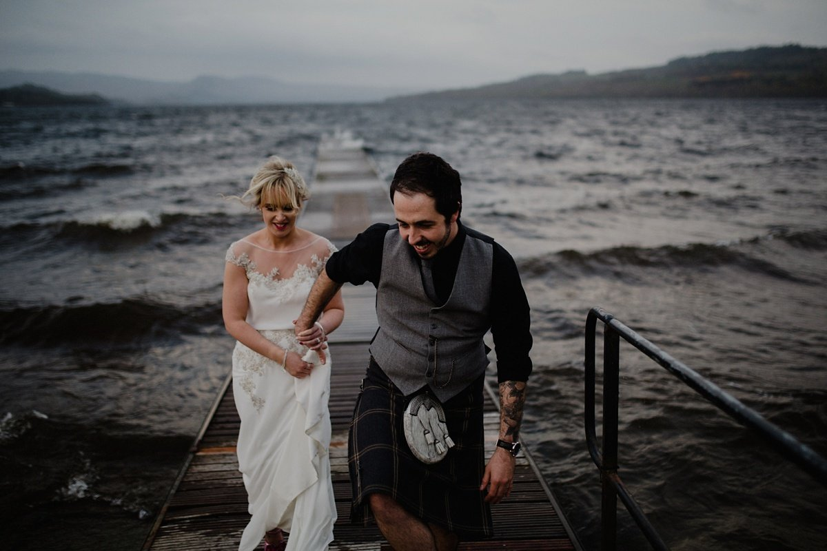 groom leads bride away from the jetty at their wedding at the cruin, loch lomond