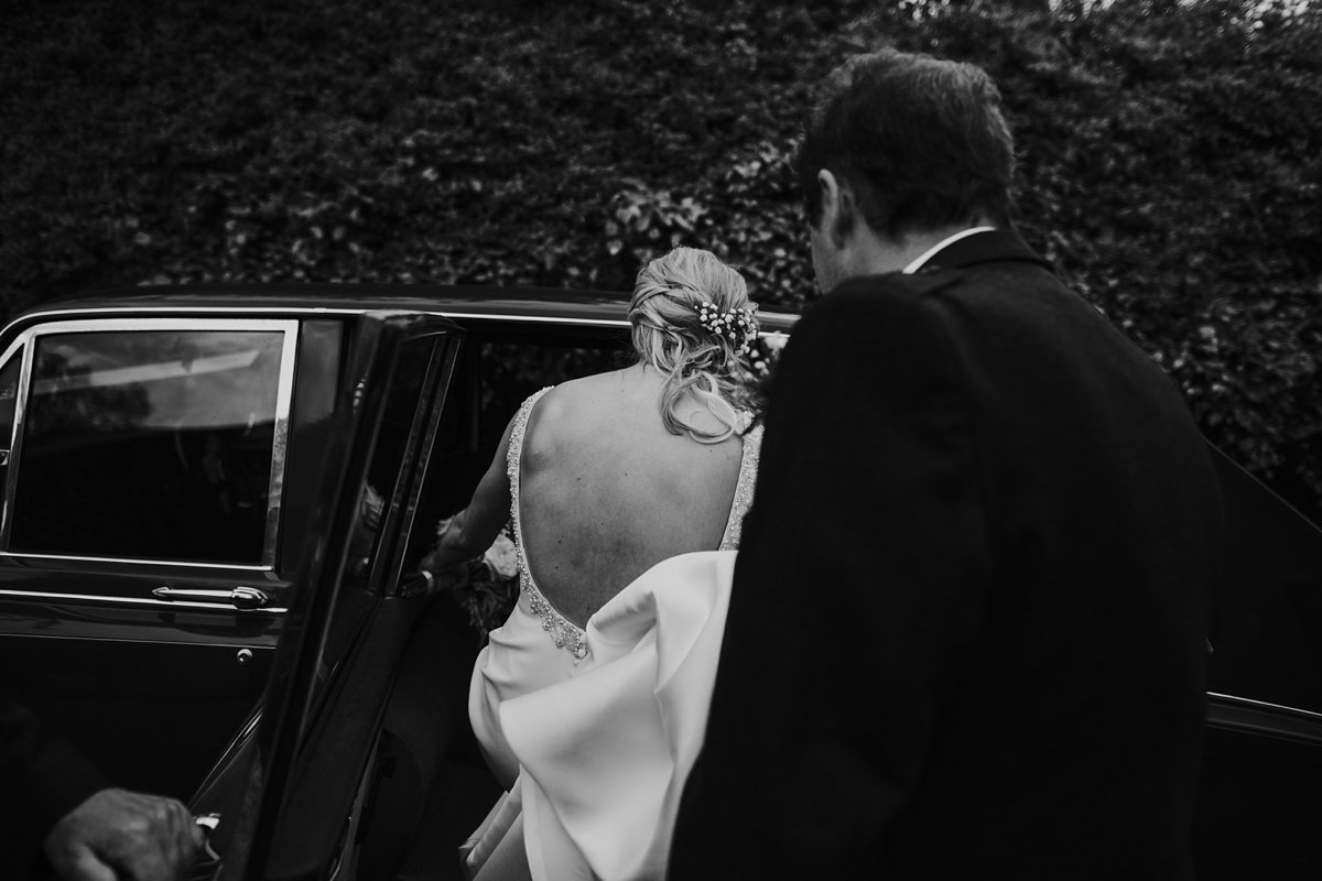 bride getting into the car to go to her wedding ceremony at melrose abbey she wears a backless wedding dress