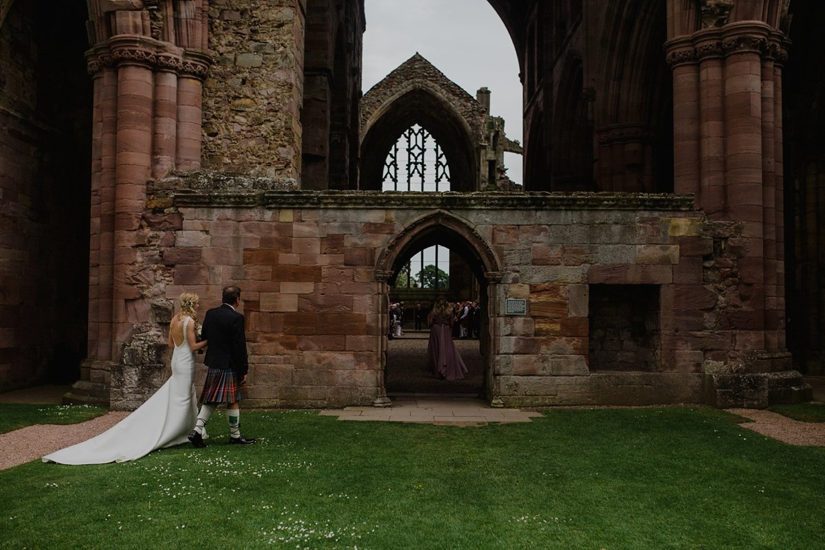 bride and her father approaching melrose abbey for her wedding ceremony