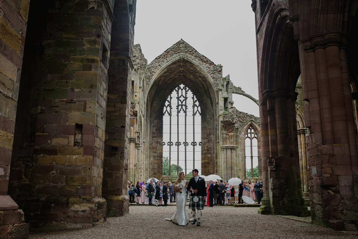 Wedding couple walking away from their ceremony at melrose abbey