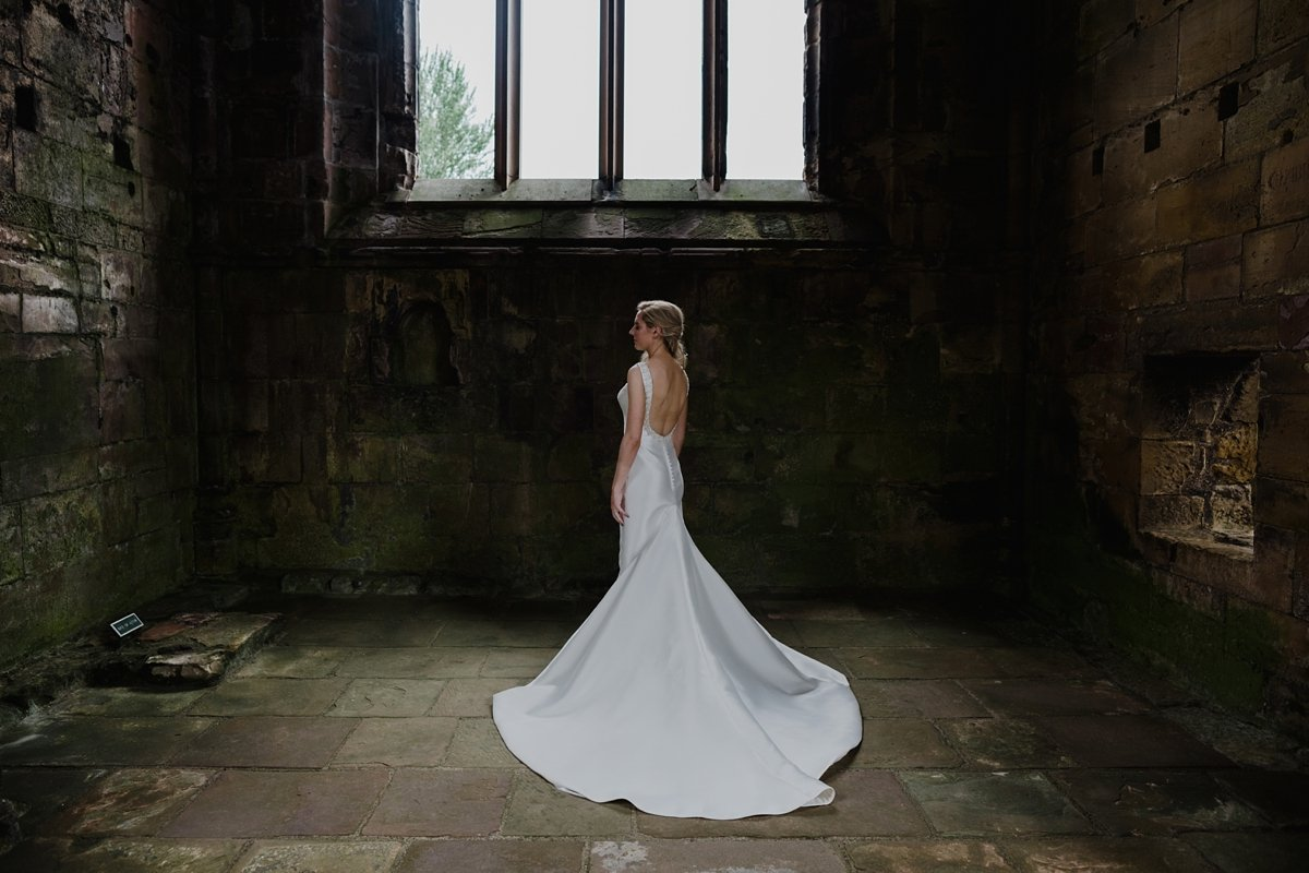bride in backless dress in the ruins of melrose abbey wedding