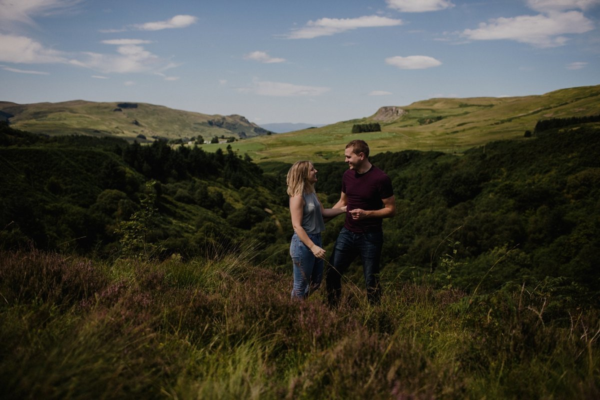Couple laughing during their Fintry engagement photography session with the Fintry Hills as a backdrop