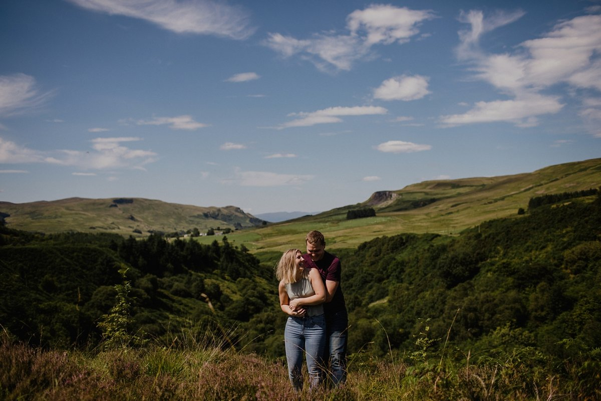 couple on their fintry engagement session in the campsie fells blue skies for their summer engagement