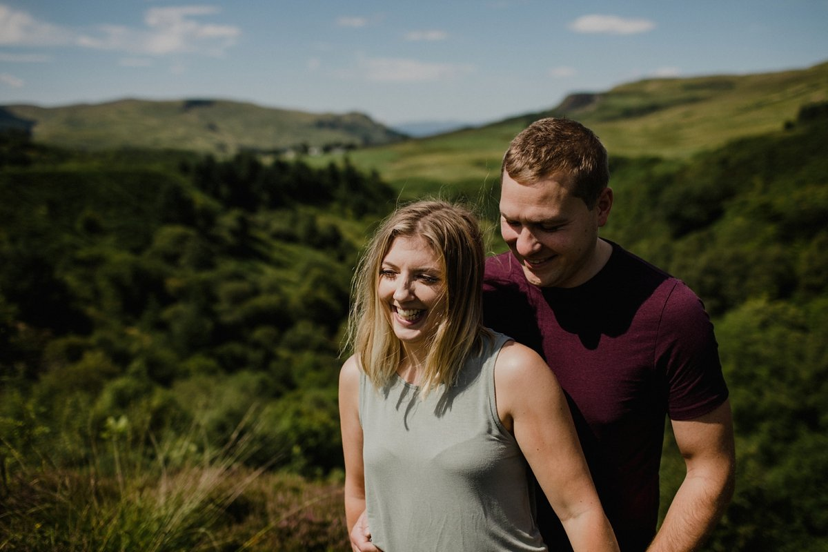 Couple laughing in the sun on their engagement session campsie fells and fintry hills in the background, hot summers day with blue sky