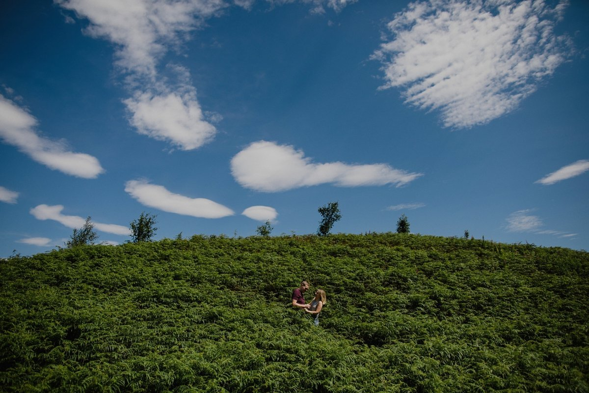 couple laughing on a hillside covered in ferns. Bright blue sky and fluffy white clouds.