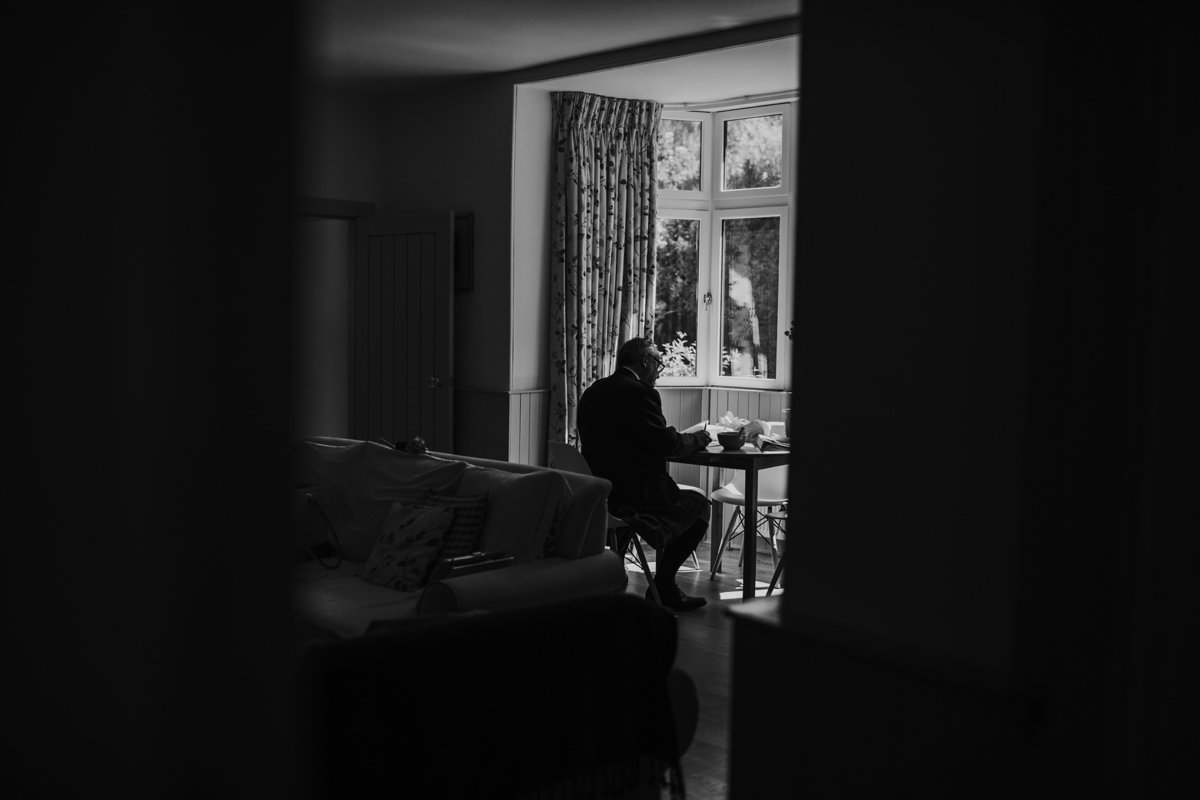 father of the bride writing his speech by the window