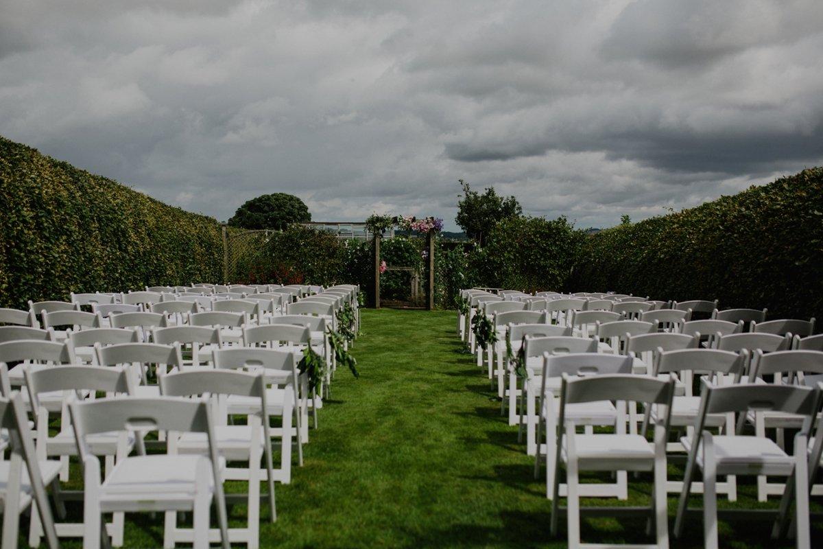 garden wedding ceremony setup with flower arch
