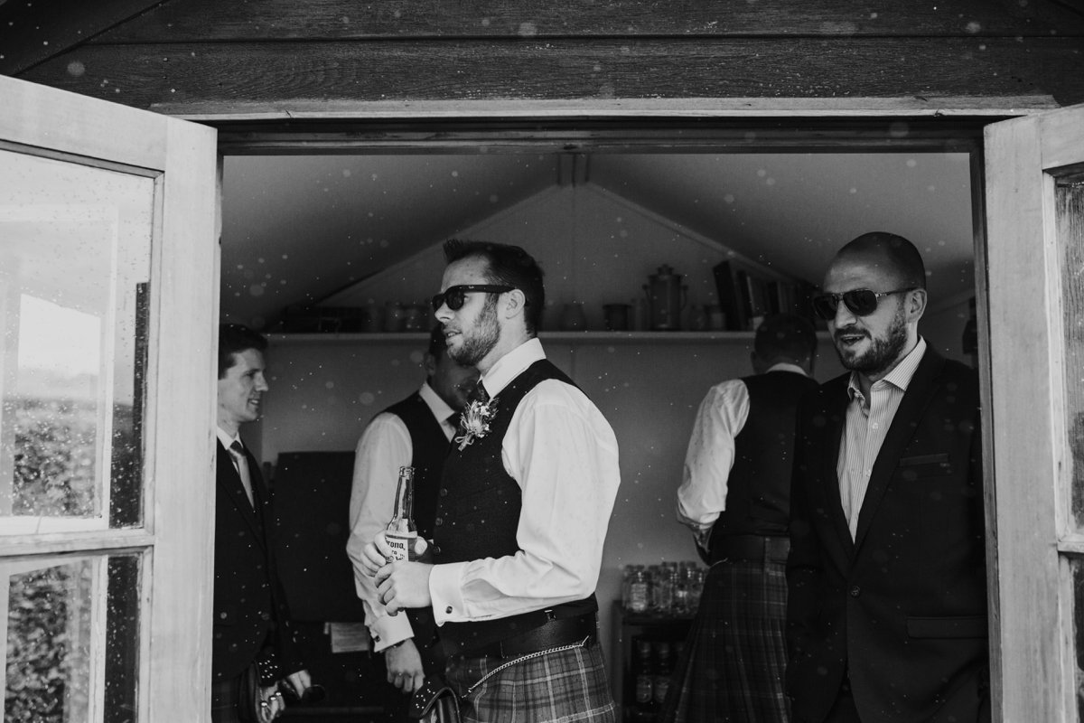 groomsmen drinking beer in garden shed sheltering from the rain