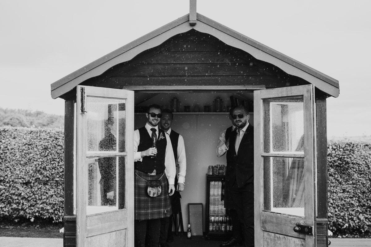 groomsmen sheltering from rain in garden shed