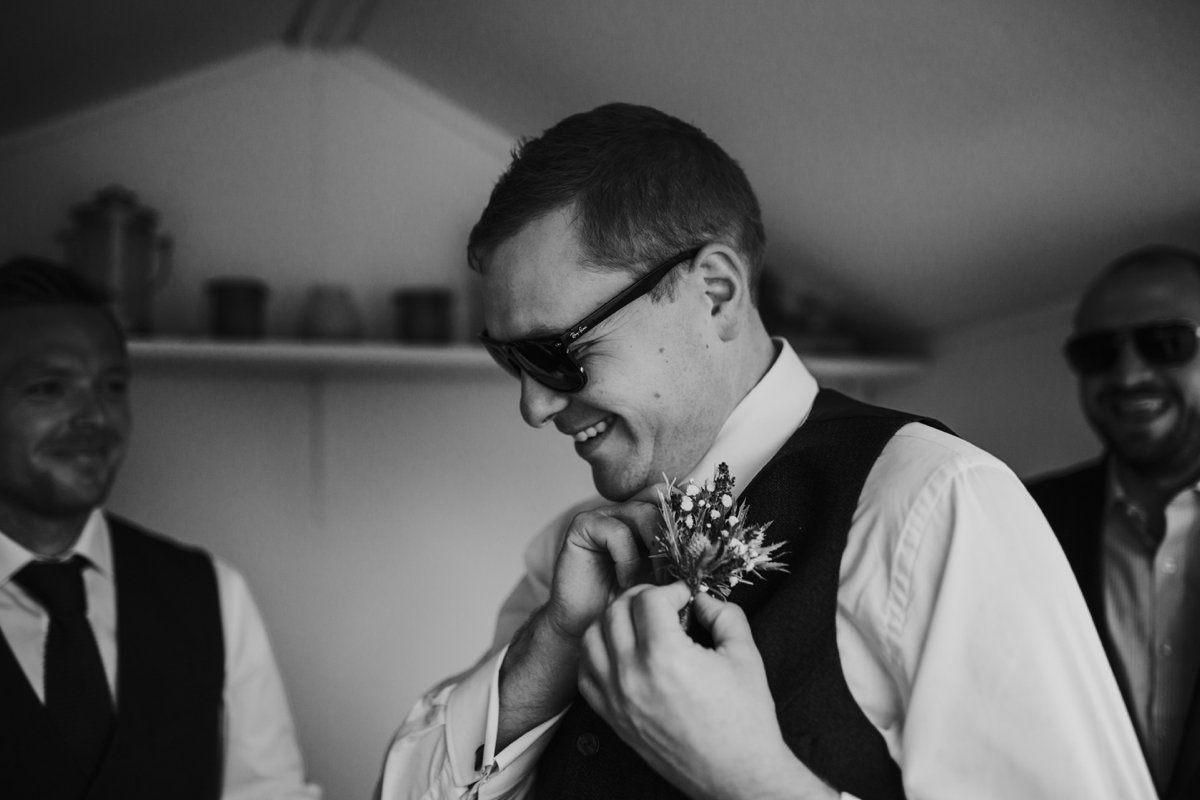 groom smiling putting on buttonhole with sunglasses