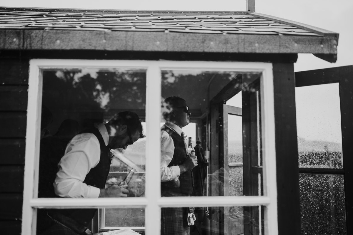 groom looking out to garden from the shed looking through the window