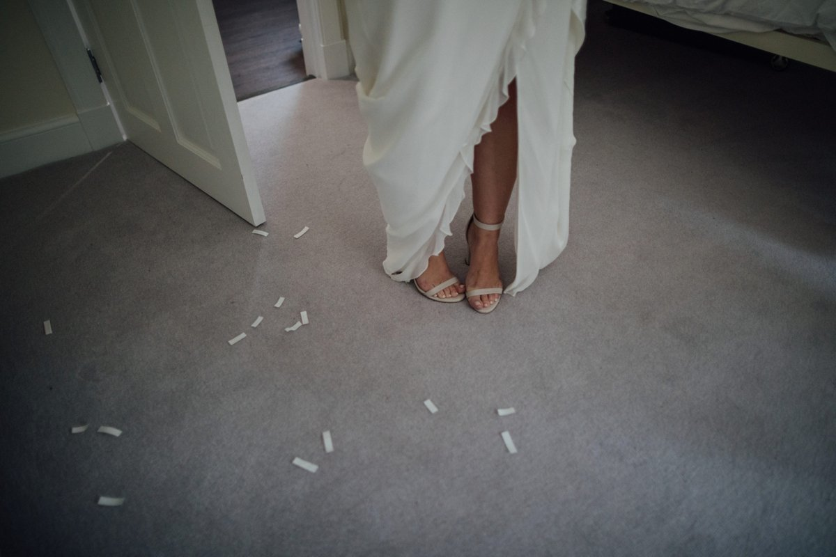 bride standing on carpet with confetti on the floor
