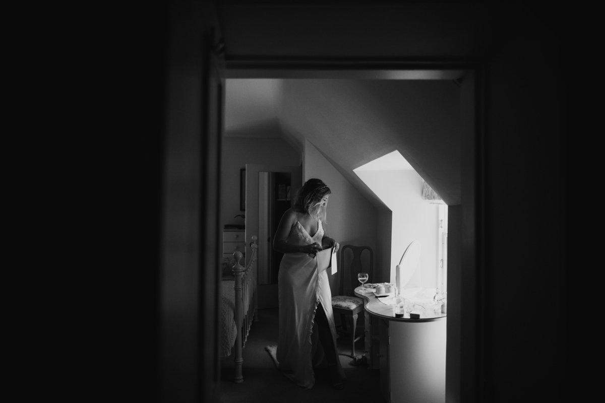 bride in window light putting some things in her bag