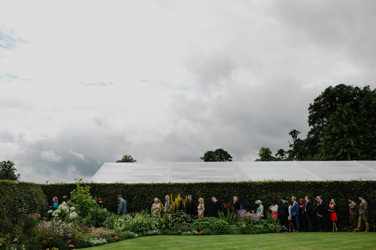 guests queuing for the garden wedding ceremony marquee in background