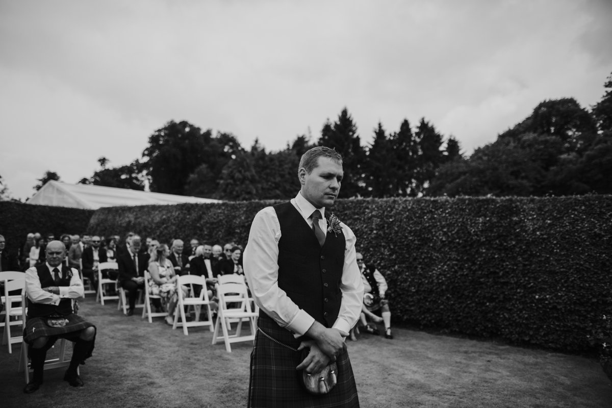 groom waiting for bride at their garden wedding ceremony