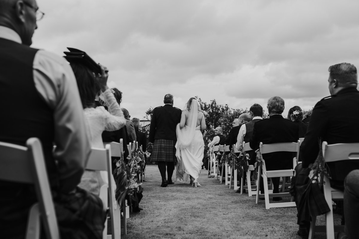 bride and bride's father walking her up the aisle for her garden wedding ceremony