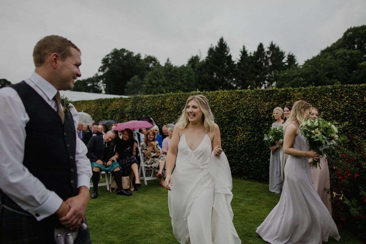 bride smiling as she sees groom for the first time at garden wedding ceremony