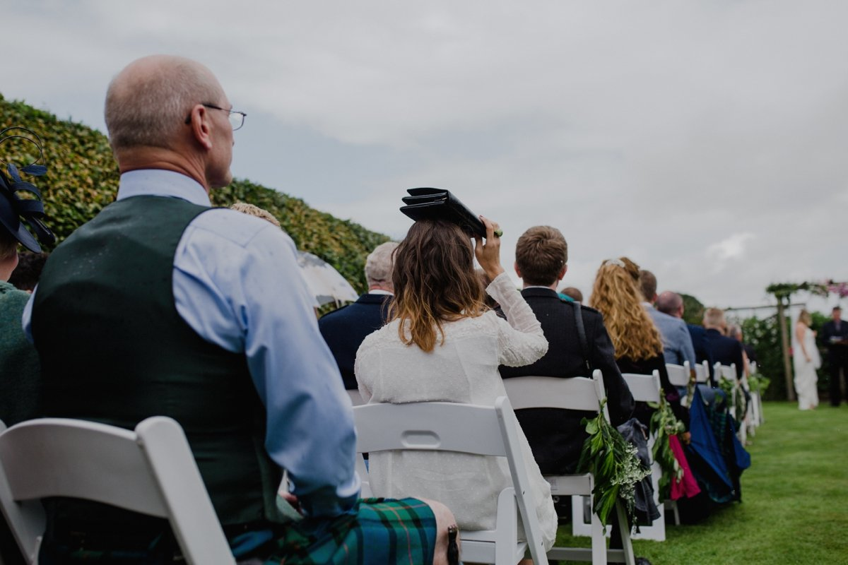 guest holding bag over head to shelter from the rain during wedding ceremony