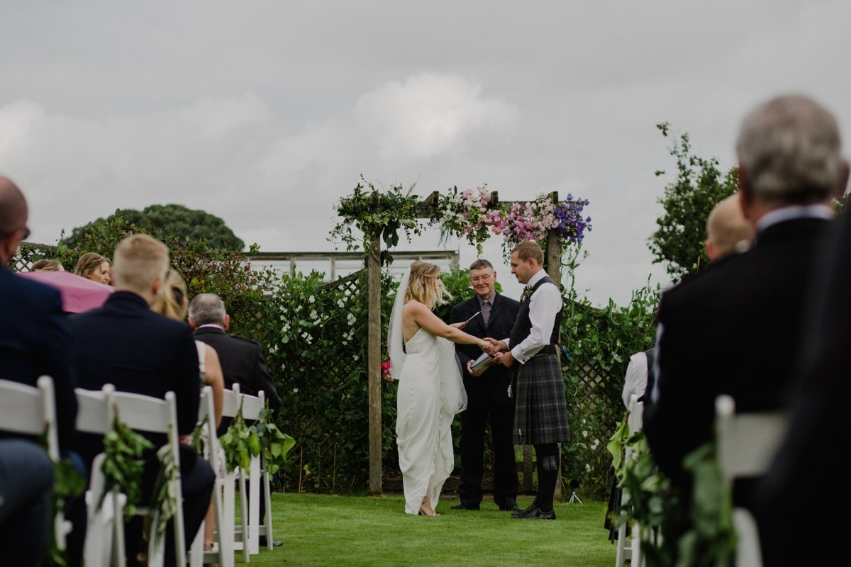 garden wedding ceremony with floral arch