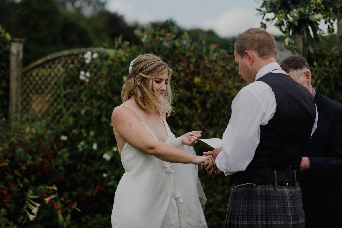 groom reading vows during garden wedding ceremony