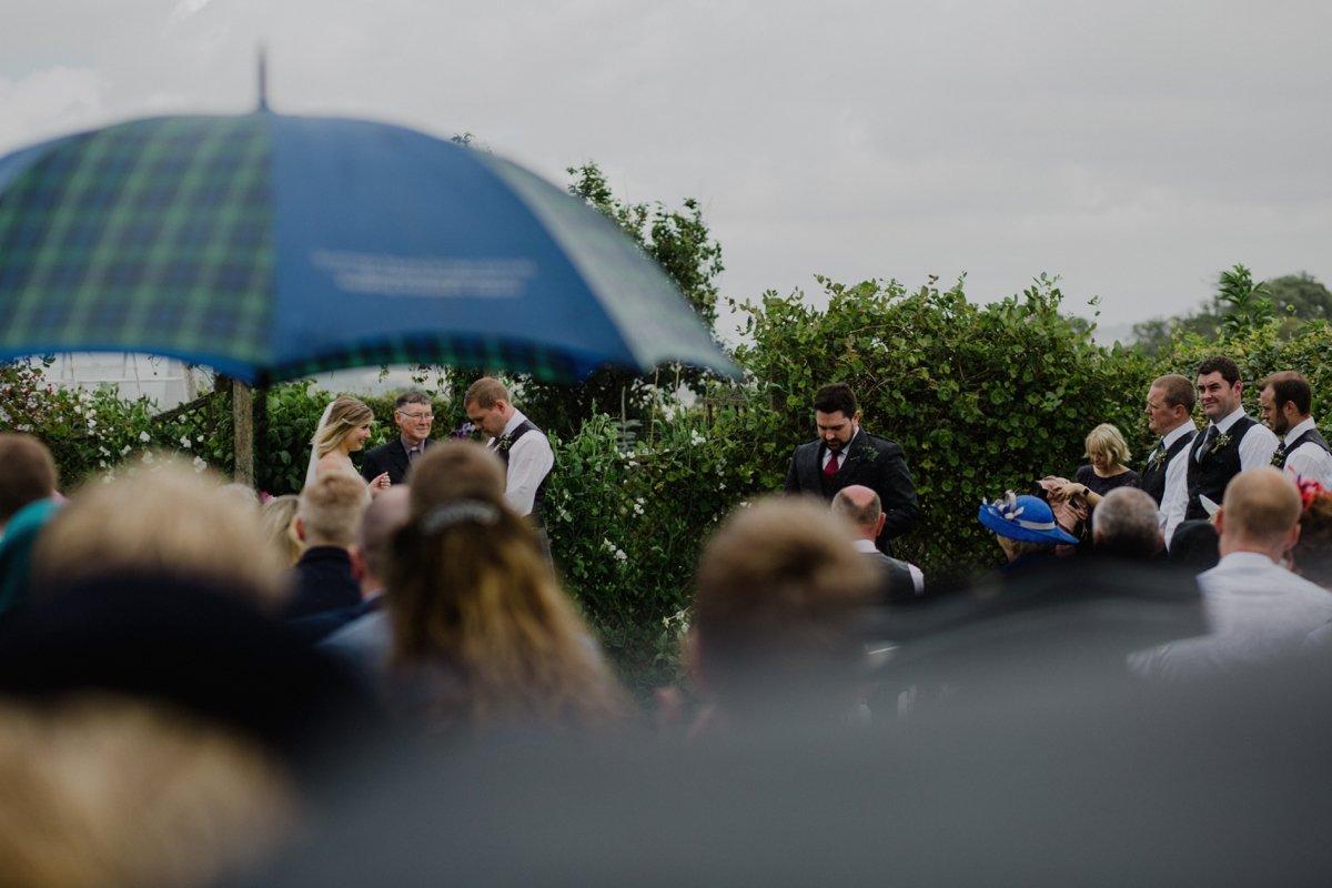 guests holding umbrella during garden wedding ceremony