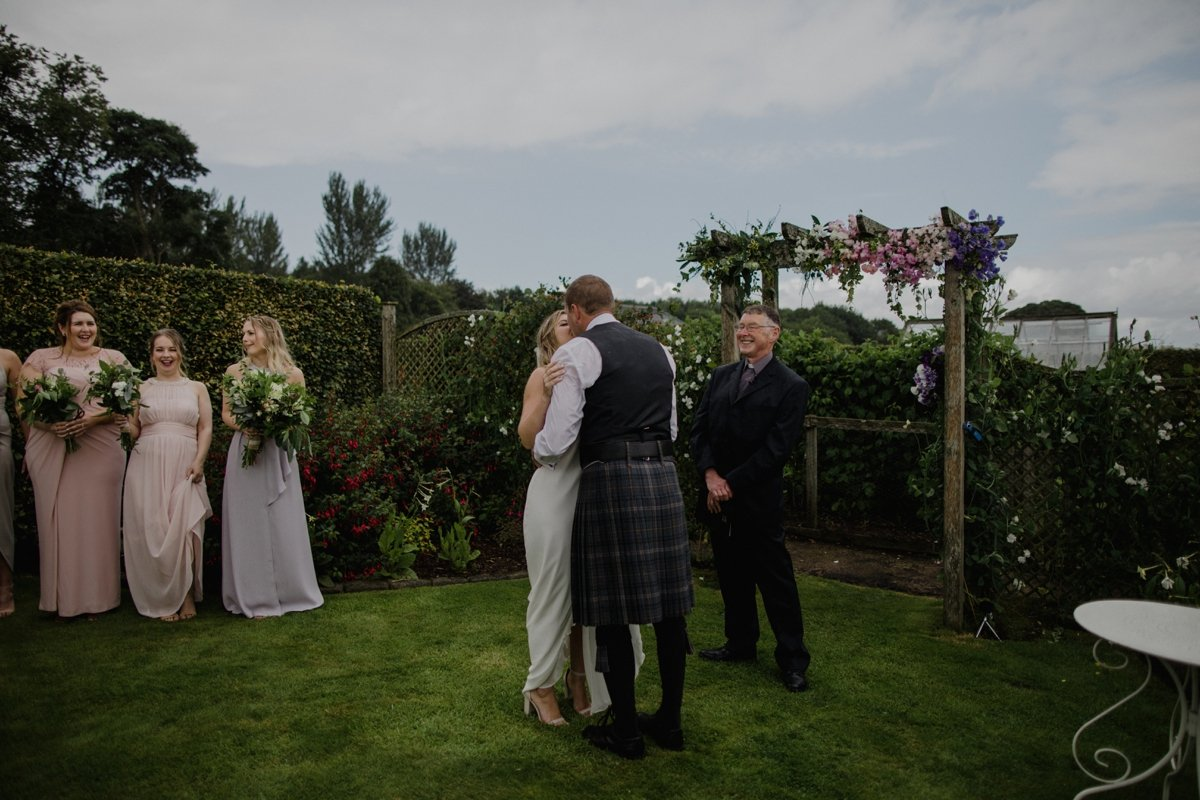 first kiss under flower arch during their garden wedding ceremony