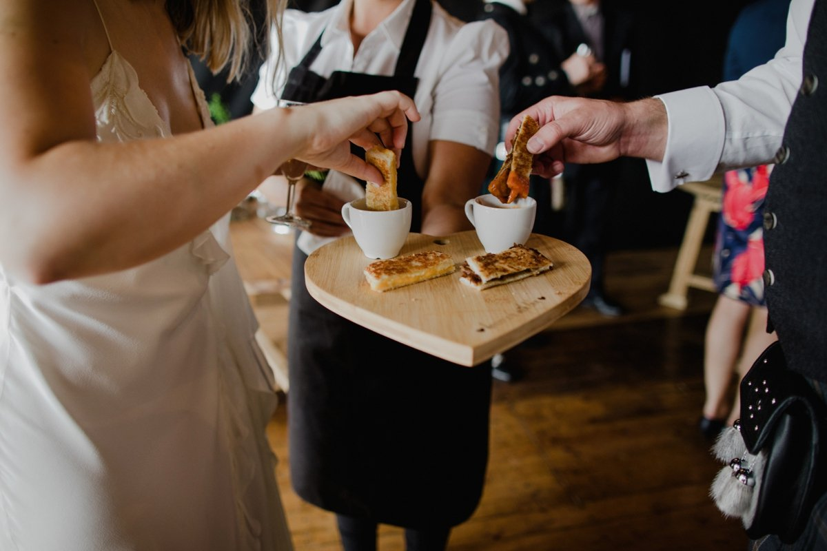 bride and groom share cups of tomato soup and toast dippers