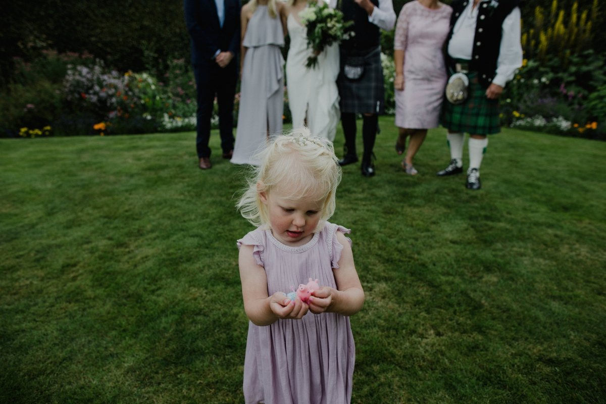 flower girl with toys wedding guests pose for group photo in background