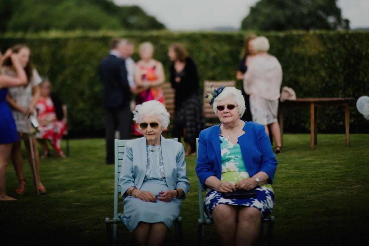 two grannies sat in the garden enjoying the wedding reception