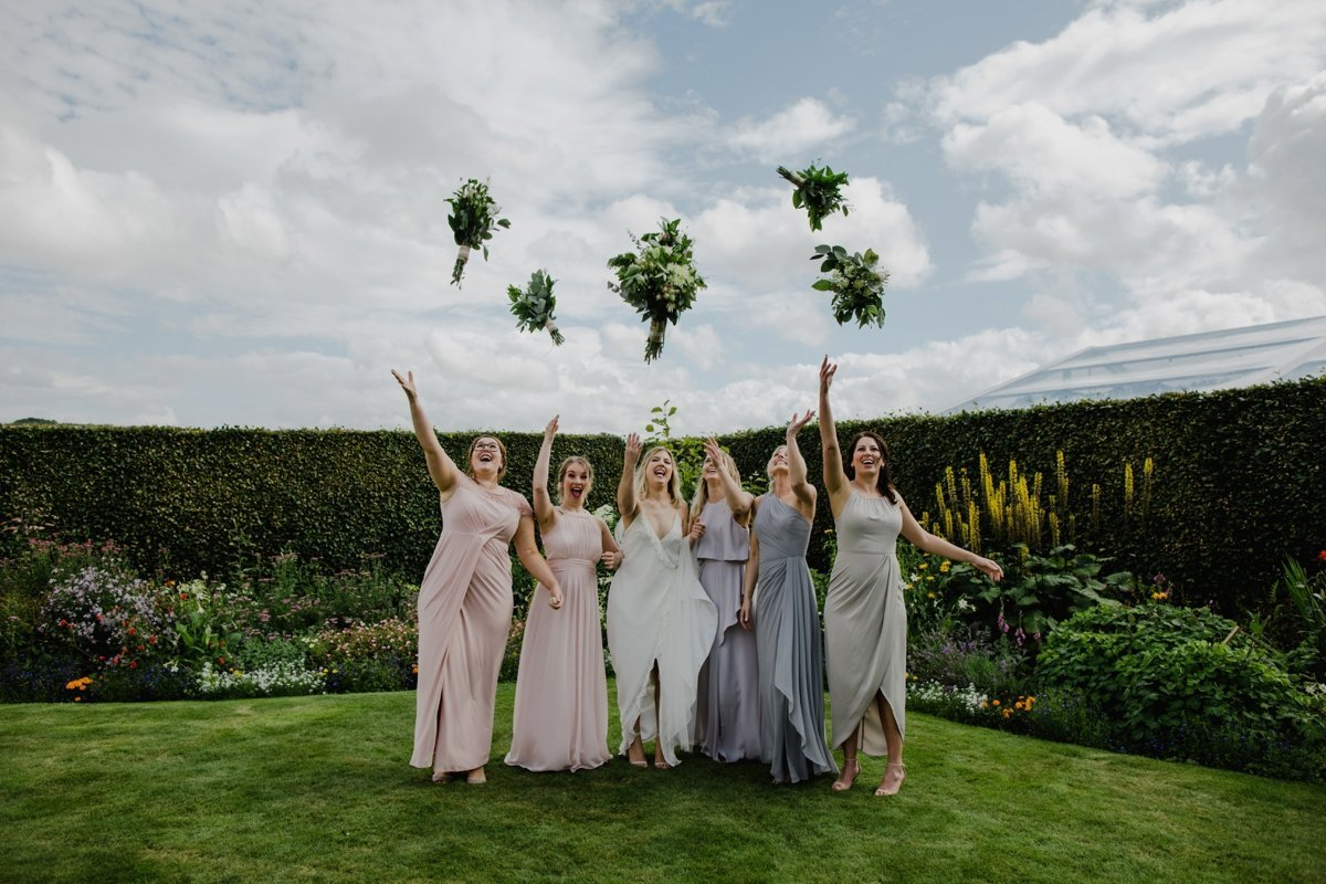 bride with bridesmaids throwing their bouquets in the air garden wedding