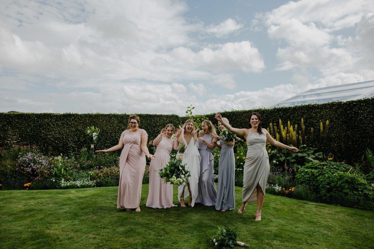 bridesmaids catching bouquets garden wedding