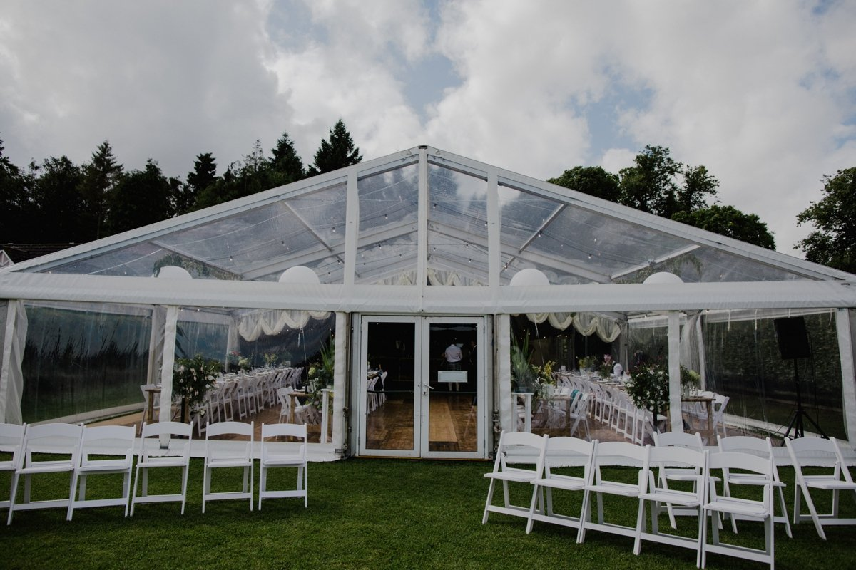 white chairs setup outside the clear span marquee