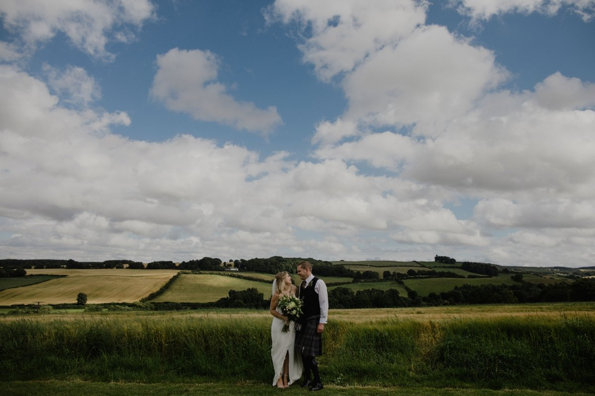 bride and groom standing in hay field blue skies fluffy white clouds garden wedding reception