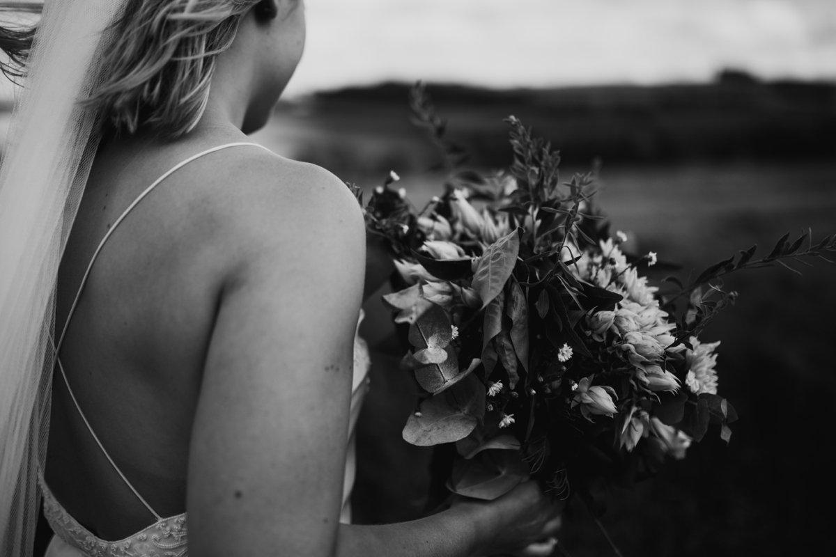 closeup of bride holding her bouquet bo & luca minimalist dress