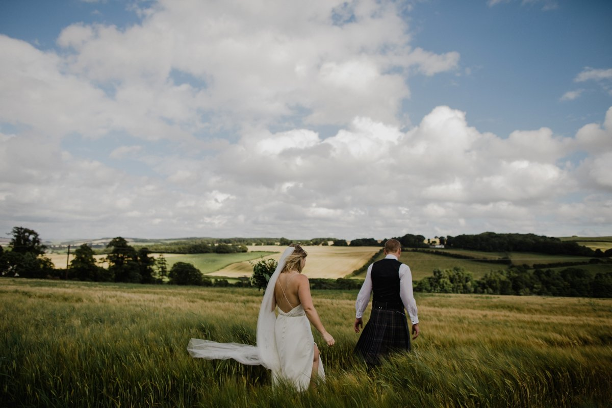 bride and groom walking through hay field blue skies fluffy white clouds garden wedding reception