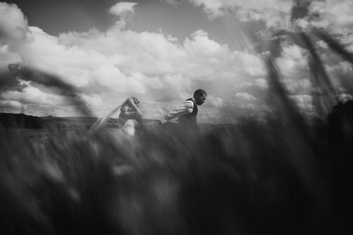 bride and groom wandering through the hay fields garden wedding