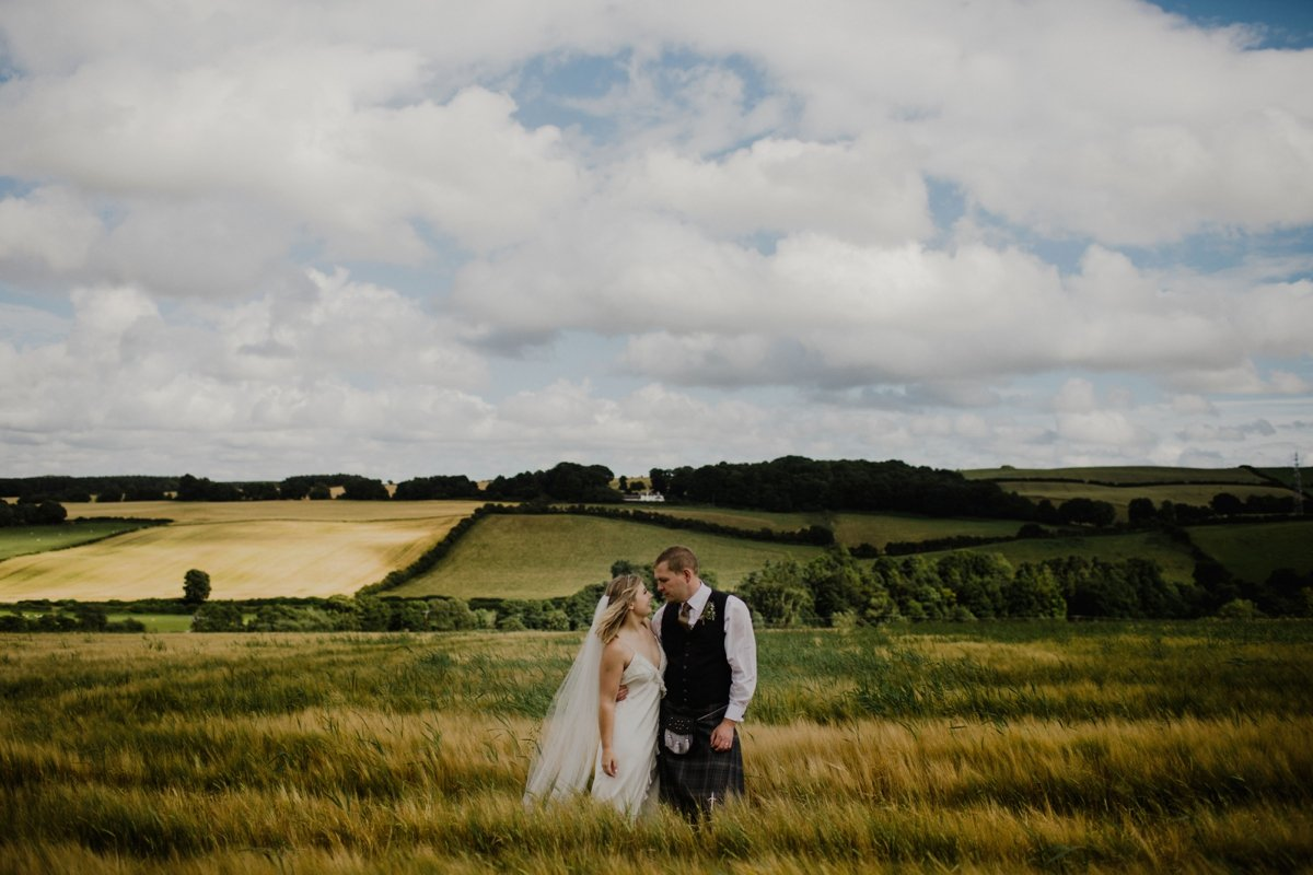 bride and groom standing in field surrounded by rustic countryside landsape blue skies fluffy clouds