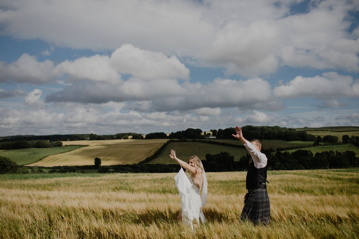couple wave to their guests from the hay field amongst the rustic countryside of the Scottish Borders