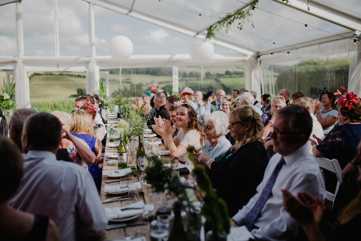 wedding guests clapping clear span marquee greenery lanterns sunshine