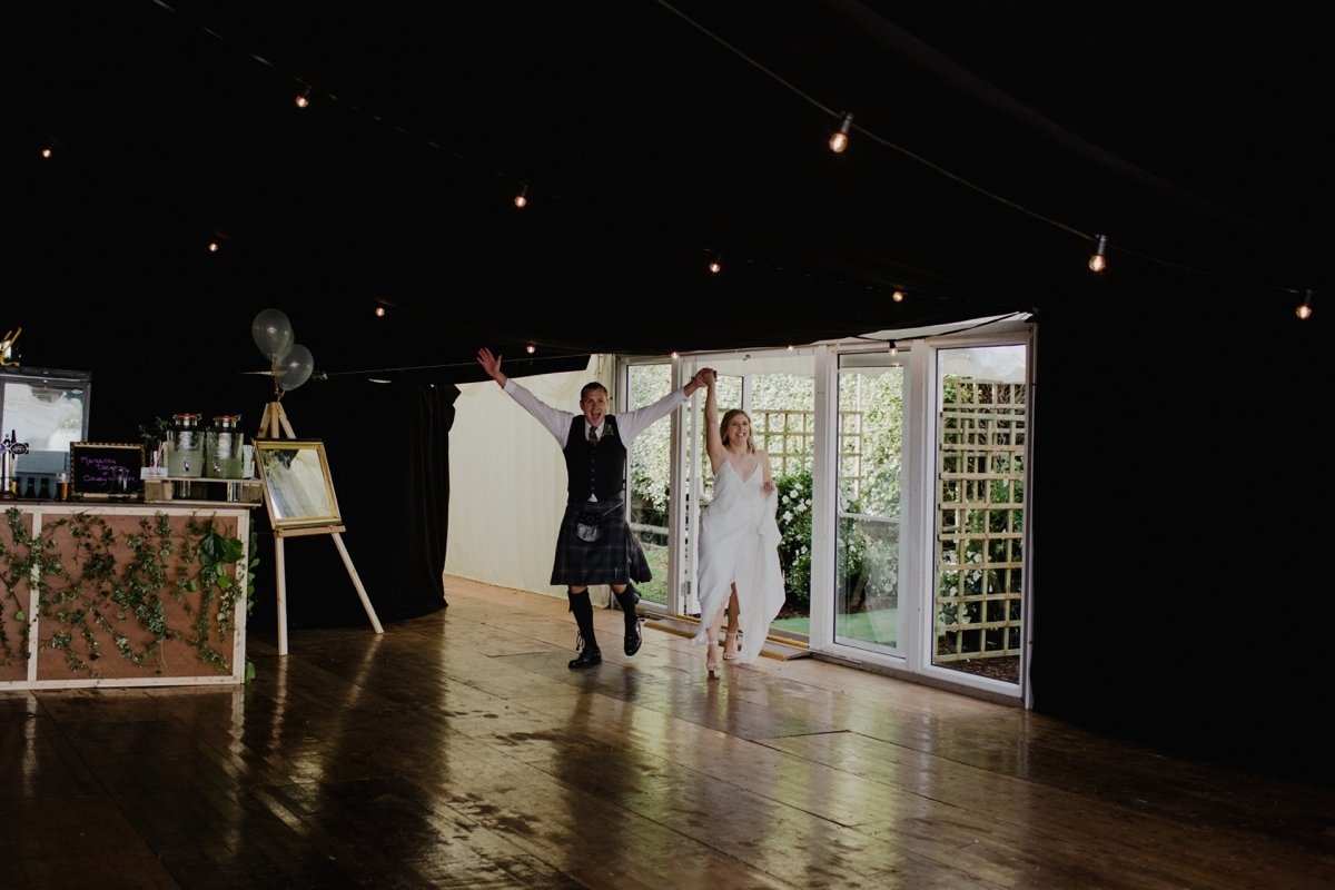bride and groom making a grand entrance to the marquee