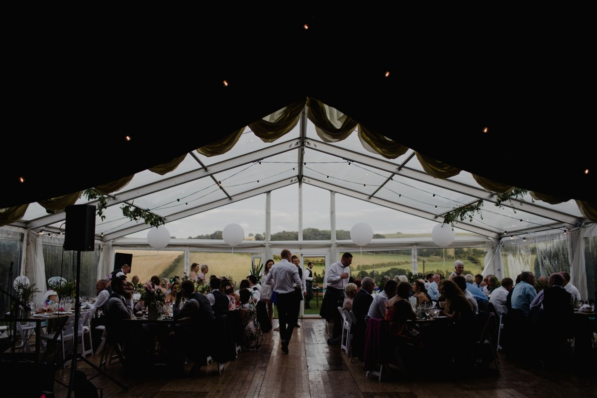 guests enjoy meal in clear span marquee