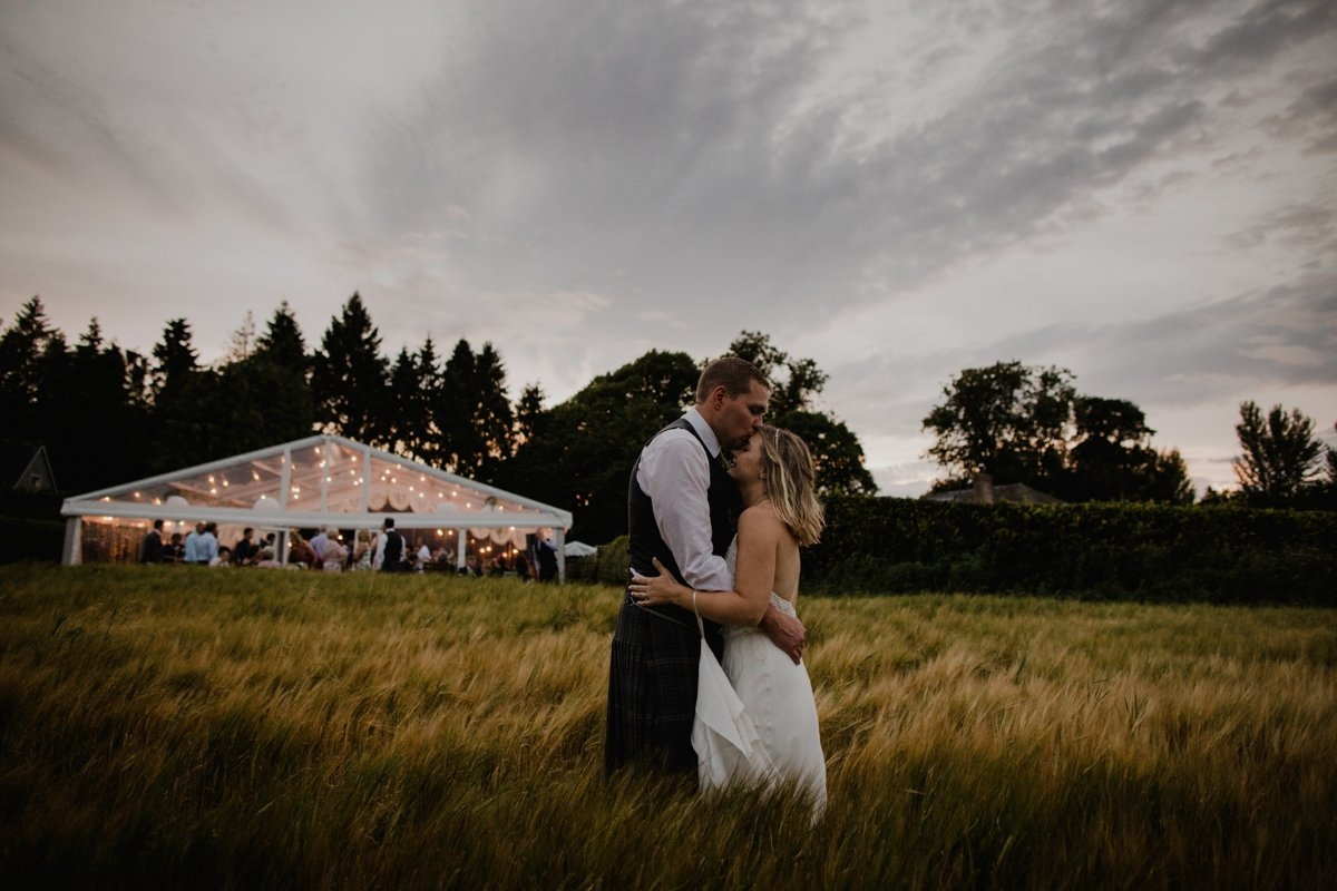 couple in front of their clear span marquee in the hay field at their garden wedding