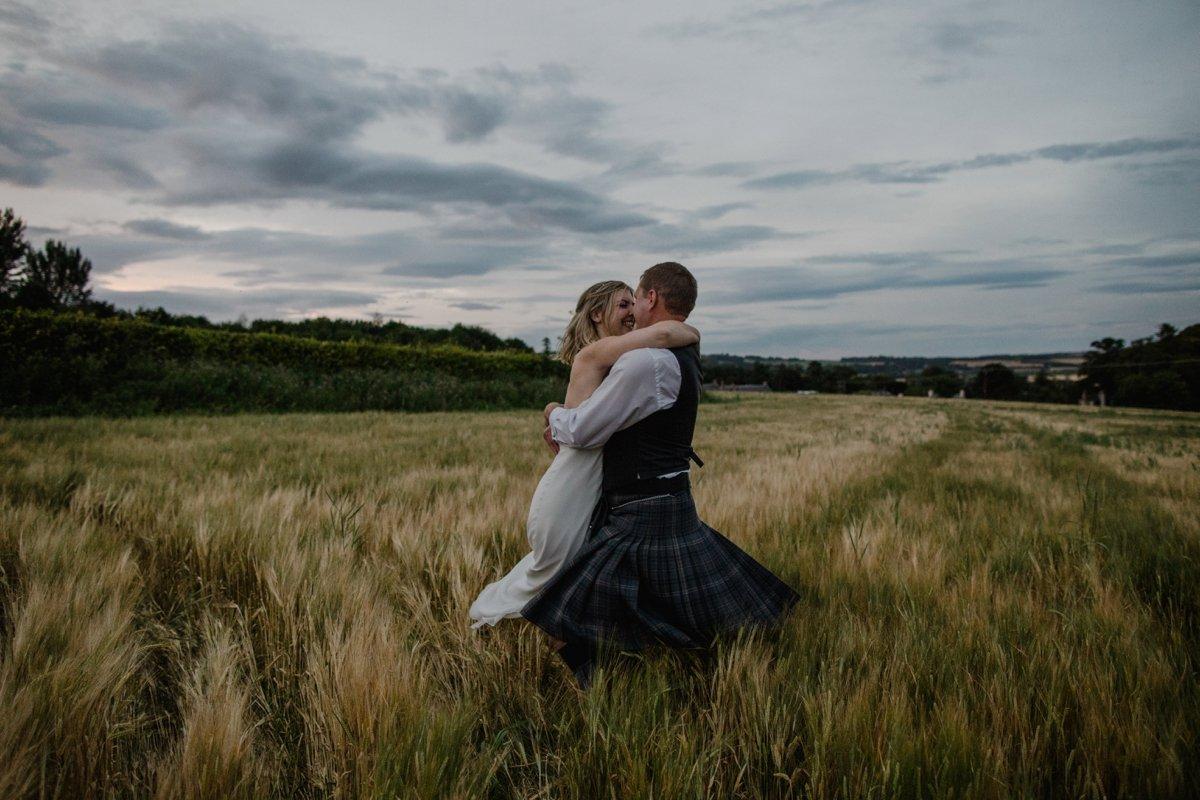 bride and groom dancing in hay field