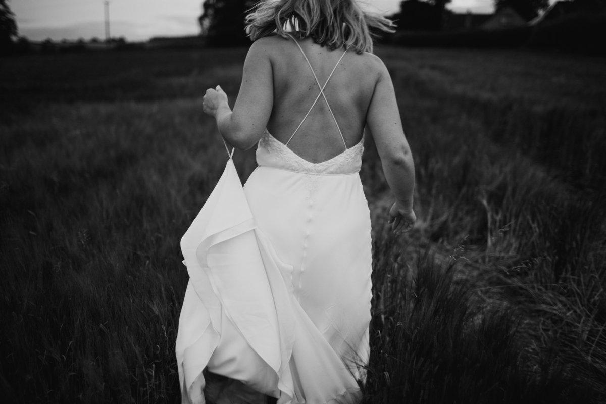 bride wearing dress by bo & luca running through the fields outside their garden wedding reception