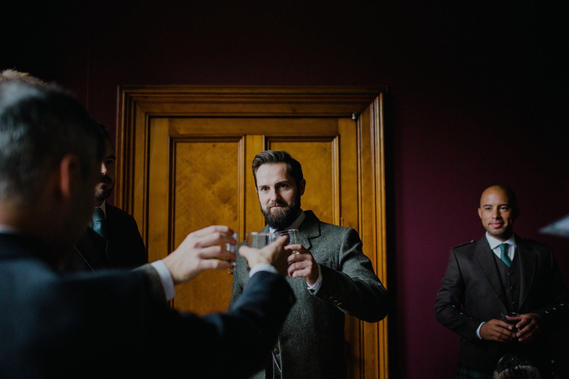 groom saying cheers with his groomsemen
