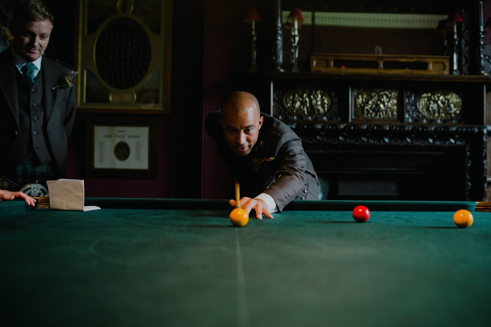groomsman playing pool in the billiard room at cambo house